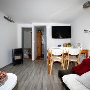 Zeigt Fernseher, Esstisch und die Türen zu den Schlafzimmern.